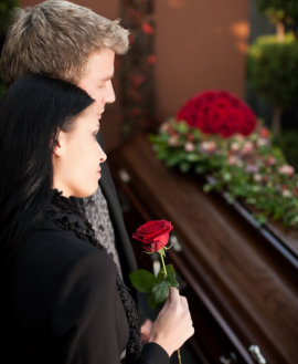 man and woman standing in front of casket